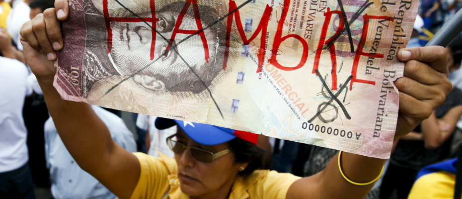 "Opposition supporter holds up a giant hundred Bolivares note with the word, ""Hungry"" written on it during a gathering to protest against the government of Venezuela's President Nicolas Maduro, and economic insecurity and shortages, in Caracas"